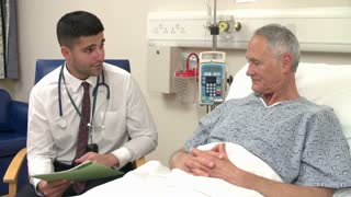 Doctor Sitting By Senior Male Patient's Bed In Hospital