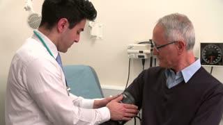 Doctor Taking Senior Male Patient's Blood Pressure
