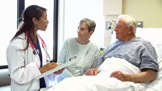 Doctor Talking To Senior Couple In Hospital Room