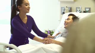Doctor Talks To Husband And Wife In Hospital Room