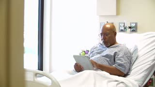 Doctor Talks To Senior Male Patient In Hospital Room