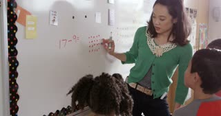 Elementary school math teacher works with kids at whiteboard