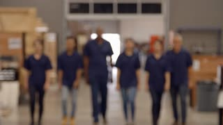 Engineers And Apprentices Walk Towards Camera In Factory