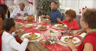 Extended family group sitting around table and enjoying Christmas meal together