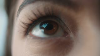 Extreme close up of a woman�s brown eye opening, looking up