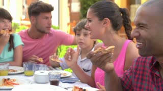 Families Eating Meal At Outdoor Restaurant Together