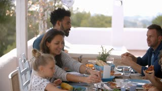 Families Enjoying Outdoor Meal On Terrace Together