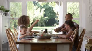 Family At Home Eating Meal In Dining Room Together