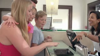 Family Checking In At Hotel Reception Using Digital Tablet