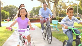 Family Riding Bikes Through Summer Park