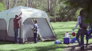 Family Setting Up Tent On Camping Holiday In Countryside