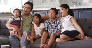 Family Sitting On Sofa At Home Watching TV Shot On R3D