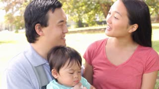 Family With Baby In Carrier Walking Through Park