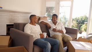Father And Adult Son Take A Break With Coffee On Moving Day
