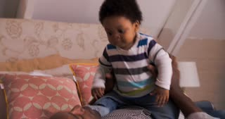 Father And Baby Son Bouncing On Bed Together