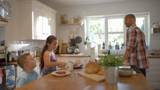 Father And Children At Home Eating Breakfast In Kitchen