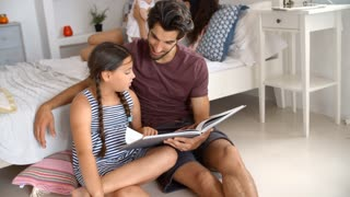 Father And Daughter Sitting In Bedroom Reading Book Together