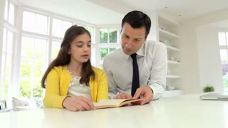 Father Helping Daughter With Homework In Kitchen