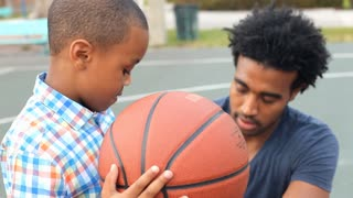 Father Teaching Son How To Throw Basketball