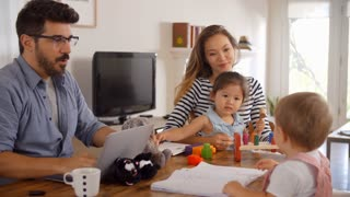 Father Uses Laptop Whilst Mother Plays With Children At Home