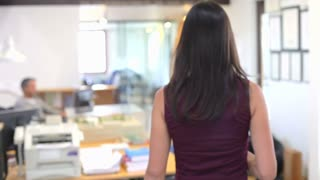 Female Architect Walks Through Office Talking To Colleagues