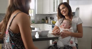 Female couple in the kitchen with their baby girl on knee, shot on R3D