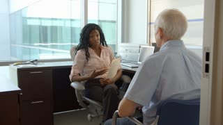 Female Doctor In Meeting With Male Patient In Office