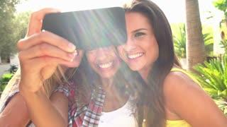 Female Friends Taking Selfie On Mobile Phone In Slow Motion