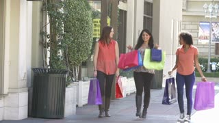 Female Friends Walking Through Mall With Shopping Bags