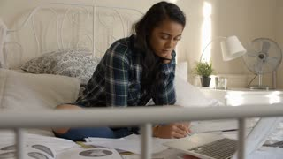 Female Student Sitting On Bed Studying With Notes And Laptop