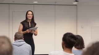 Female teacher addressing university students in class, shot on R3D