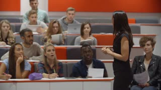 Female teacher and students in university lecture theatre