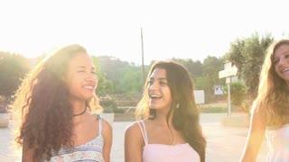 Female Teenage Friends Walking Along Street In Slow Motion