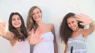 Female Teenage Friends Waving At Camera In Slow Motion