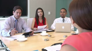 Four Businesspeople Having Meeting Around Boardroom Table