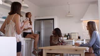 Four female friends drinking wine and talking in kitchen, shot on R3D