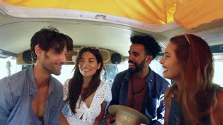 Four friends on a road trip talk in the back of a camper van