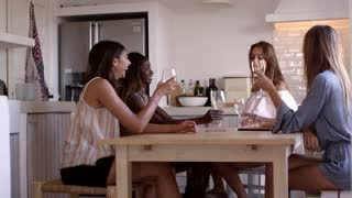 Four women drink wine at kitchen table at a girls� night in, shot on R3D