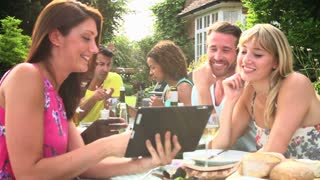 Friends Having Barbeque At Home Looking At Digital Tablet