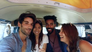 Friends in the back of a camper van on a trip taking selfie