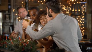 Friends making a toast at a Christmas party in a bar