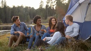 Friends on a camping trip relaxing by their tent near a lake