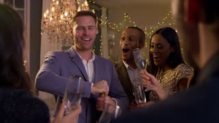 Friends Open Champagne As They Celebrate At Party Together