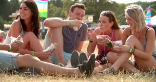 Friends sit on grass, eating and talking at a music festival