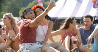 Friends sitting on grass taking selfie at a music festival