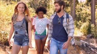 Friends talking as they walk through a forest, front view
