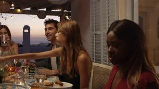 Friends talking at a dinner party on a roof terrace, Ibiza, shot on R3D
