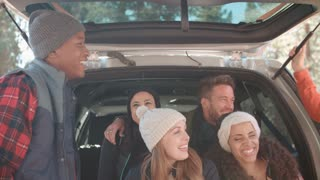 Friends talking at the open back of a car, close up