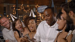Friends uncorking champagne at a New Year�s party at a bar