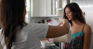 Gay female couple talking over breakfast in their kitchen, shot on R3D